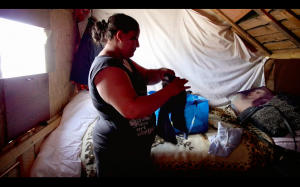"Photo credit: screen shot from the documentary ""Ett bättre liv"", SVT episode 5. Carmen packing up her belongings in a camp in Malmö, about to return to her home country of Romania."
